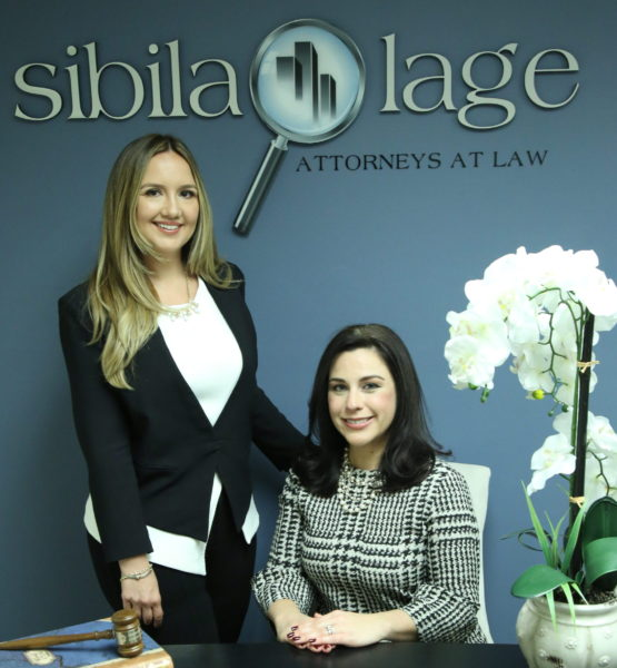 Image of Sibila Lage Attorneys At Law. Photo of Estrellita S. Sibila (left) standing next to seated Jacqueline M. Lage (right). On table, gavel on top of law book (left) and orchids (right).